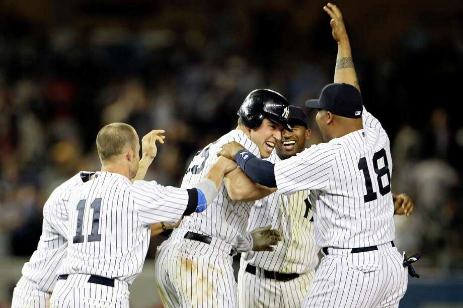 NEW YORK, NY - MAY 24:  Mark Teixeira #25 of the New York Yankees celebrates with Brett Gardner #11 and Andruw Jones #18 after hitting a game winning RBI in the ninth inning against the Toronto Blue Jays at Yankee Stadium on May 24, 2011 in the Bronx borough of New York City.  (Photo by Michael Heiman/Getty Images) Photo: Michael Heiman