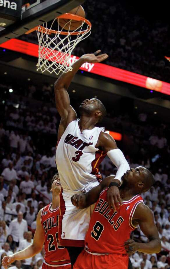 Miami Heat's Dwyane Wade (3) goes for a basket between Chicago Bulls' Luol Deng (9) and Kyle Korver (26) during the first half of Game 4 of the NBA Eastern Conference finals basketball series in Miami, Tuesday, May 24, 2011. (AP Photo/Lynne Sladky) Photo: Lynne Sladky