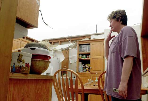 Amy Gilbert stands in what is left of her kitchen Tuesday, May 24, 2011, in Joplin , Mo. Gilbert and her husband, Eric, were standing in the kitchen as the roof began to tear away from the house during a tornado Sunday night.  The couple was able to seek shelter in a bathroom off the kitchen along with their eight-year-old daughter their dogs and a friend.  All survived without injury.   (AP Photo/Jeff Roberson) Photo: Jeff Roberson