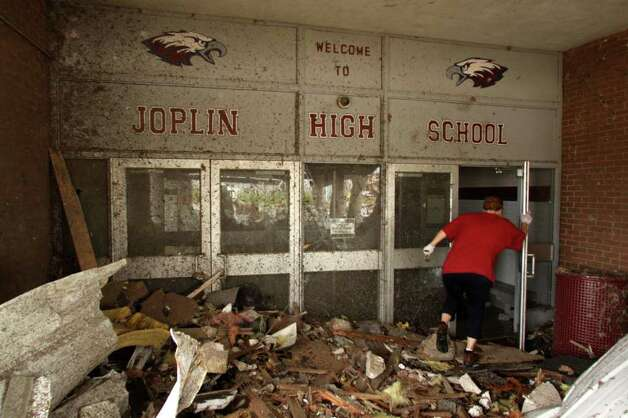 A woman makes her way into the damaged main entrance of Joplin High School in Joplin, Mo., Tuesday, May 24, 2011. At least 116 people were killed and hundreds more injured when a tornado cut a destructive path through Joplin on Sunday evening. Classes at all Joplin schools have been canceled for the rest of the schoolyear after four schools were damaged or destroyed. (AP Photo/Mark Schiefelbein) Photo: Mark Schiefelbein