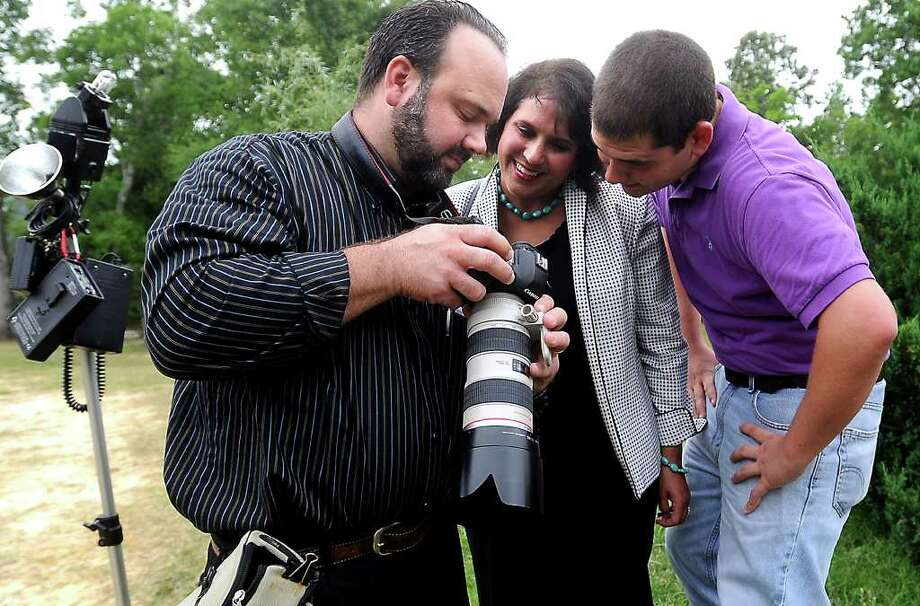 Brandon Gouthier shows raw files of West Brook student John McGinnis' senior portraits to McGinnis and his mother, Christine McGinnis, at the Beaumont Botanical Garden in Tyrrell Park  in Beaumont. Tammy McKinley/The Enterprise Photo: TAMMY MCKINLEY