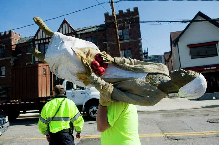 "Eddie Whitehead, an employee with city of Stamford, carries a piece of the ""Appalachia"" sculpture, by Judith Peck, down Spring Street as they install the ""Wit & Whimsy"" sculptures throughout the city in Stamford, Conn. on Wednesday May 25, 2011. Photo: Kathleen O'Rourke / Stamford Advocate"