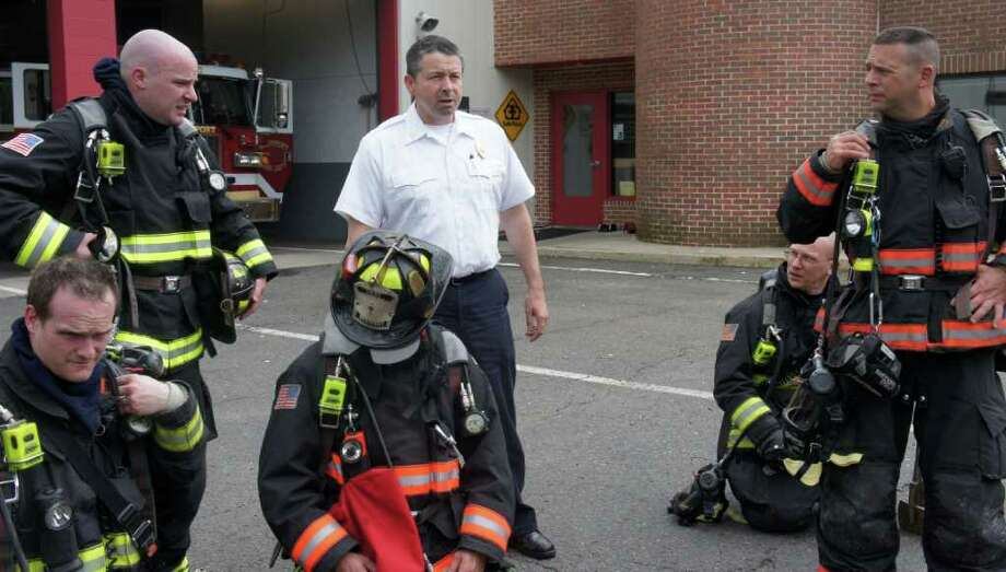 Westport Fire Chief Andrew Kingsbury, center, debriefs firefighters following a training exercise at fire department headquarters at 515 Post Road East on Tuesday, May 24, 2011. Photo: Paul Schott / Westport News