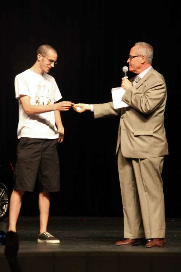 Nederland High School senior Scott Authement takes the keys of a 2011 Scion tC from Bob Thewman, general manager of Philpott Motors. Authement beat out more than 650 others in the school's annual car give away for students with good attendance. Photo: Cade Phelps, NHS