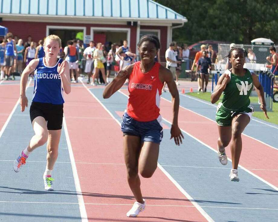 Brien McMahon's Shelly Lindo, center, wins the 100 meters at the FCIAC Track and Field Championships Tuesday at Danbury High School. Photo: Barry Horn / The News-Times Freelance