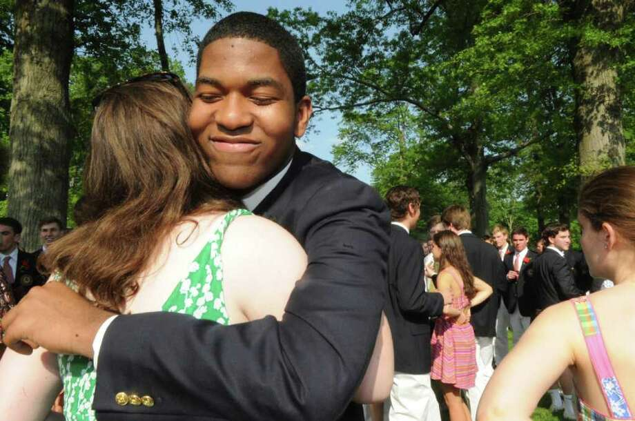 Olivia Harvey gives a hug to Allen Louis after the Brunswich school's 109th commencement on Wednesday, May 25, 2011. Photo: Helen Neafsey / Greenwich Time