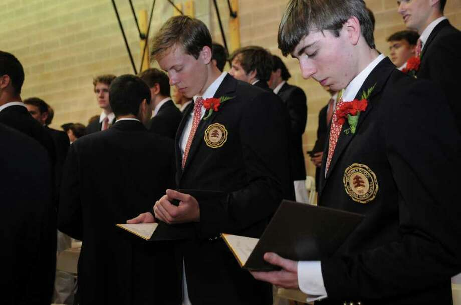 Jeffrey Robert Jay Jr., left, and Alexander Evan Graf look at their diplomas during the Brunswick School's 109th commencement on Wednesday, May 25, 2011. Photo: Helen Neafsey / Greenwich Time