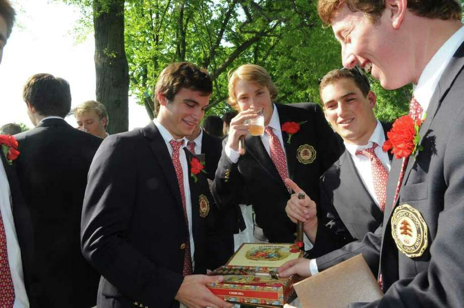 Alex Gattinella, left, passes out cigars after the Brunswick School's 109th commencement ceremony Wednesday, May 25, 2011.  Passing out cigars is a graduation tradition at the school. Photo: Helen Neafsey / Greenwich Time