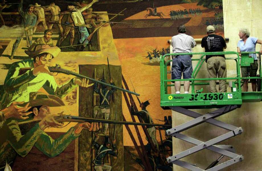 "Tony Sheets (left) takes down ""The Death of Travis,"" a mural painted by his father Millard Sheets in 1967, at the old Travis Savings and Loan Building on May 24. With Sheets is Arnulfo Hernandez (center) and Flower Sheets, his wife. Photo: Bob Owen / rowen@express-news.net"