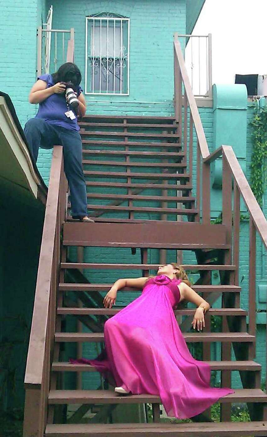 Staff photographer Helen L. Montoya lines up a photograph on the rear stairs of dance studio Calle Ocho. Conexion's 2011 Hottest Latina winner Luzelena Ortiz-Lopez models spring fashions from Macy's North Star. Photo by Tricia Schwennesen