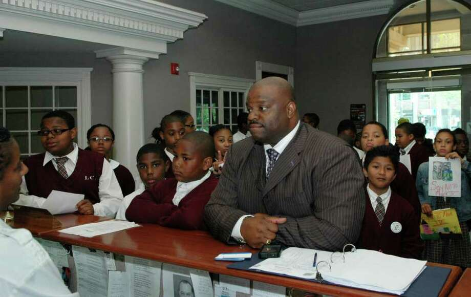 The Rev. Kenneth Moales Jr. and students from Love Christian Academy in Bridgeport, Conn. deliver letters of protest to Mayor Finch's office on Thursday, May 26, 2011. The students, administrators and supporters wanted to make clear their objection to any deal that would allow the Mark IV Construction operation on Seaview Ave. to continue. The City cited progress today in a decision by Mark IV Construction to drop its appeal of a City cease and desist order regarding its rock crushing and fill operation on Seaview Ave. which the company now agrees to close by Dec. 1, 2011. Photo: Cathy Zuraw / Connecticut Post