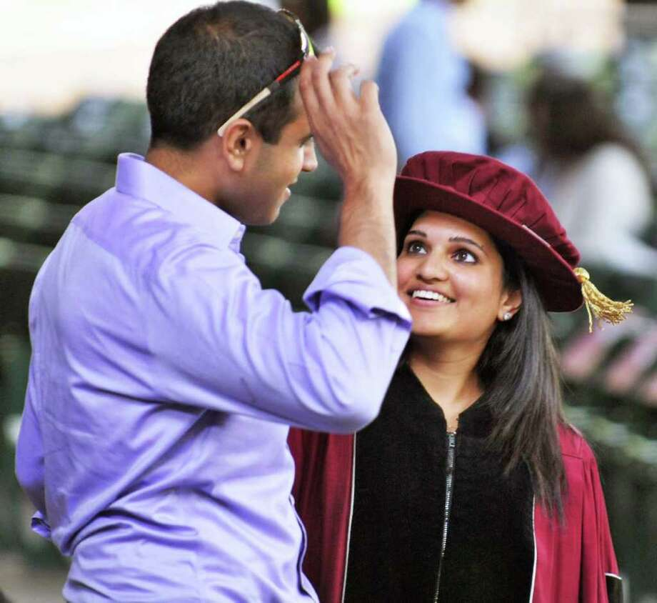 Rachna Patel of Long Island shares a moment with fiance Sid Subramony, left, of New Hampshire  before the start of the 173rd Albany Medical College commencement ceremony at SPAC on Thursday.   (John Carl D'Annibale / Times Union) Photo: John Carl D'Annibale / 00012818A