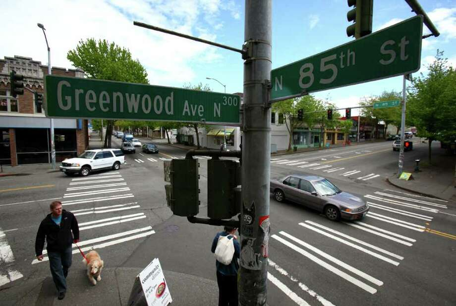 A pedestrian crosses Greenwood Avenue North at the intersection with North 85th Street in the Greenwood neighborhood. The Seattle Department of Transpotation announced a major project to repave 85th that will include rebuilding the arterial's intersections with Greenwood and Aurora Avenue North. Photographed on Thursday, May 26, 2011. Photo: JOSHUA TRUJILLO / SEATTLEPI.COM