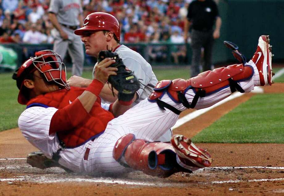Philadelphia Phillies catcher Carlos Ruiz, left, tumbles after tagging out Cincinnati Reds' Jay Bruce at home plate after Bruce tried to score on a fielder's choice by Edgar Renteria in the second inning of a baseball game on Wednesday, May 25, 2011, in Philadelphia. Renteria was safe at first. (AP Photo/Matt Slocum) Photo: Matt Slocum, STF / AP