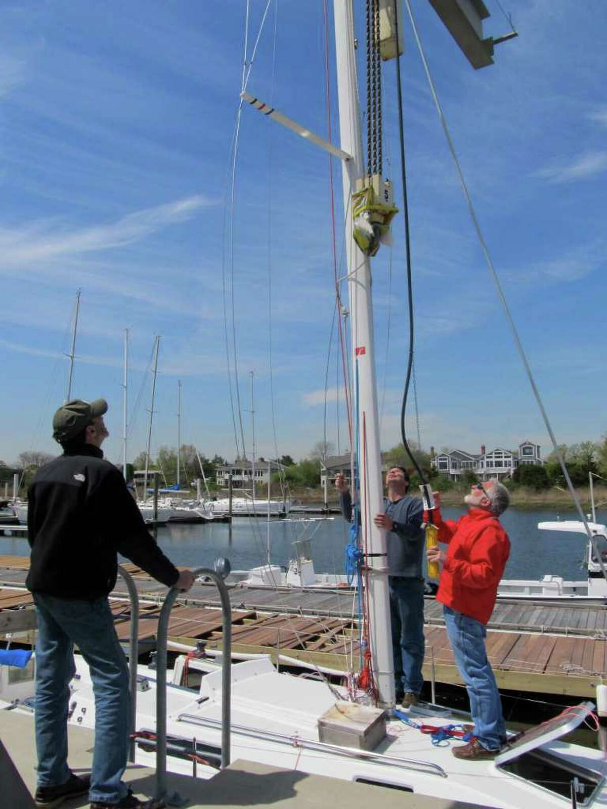 Boaters, from left to right, Bill Rivkin, Trevor Roach, and Lincoln Schoenberger put a mast on a sailboat at Cedar Point Yacht Club in Westport.