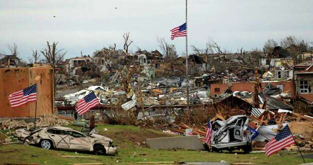A flag files at half staff over devastated Joplin High School in Joplin, Mo. Thursday, May 26, 2011. An EF-5 tornado tore through much of the city Sunday, damaging a hospital and hundreds of homes and businesses and killing at least 125 people. (AP Photo/Charlie Riedel) Photo: Charlie Riedel