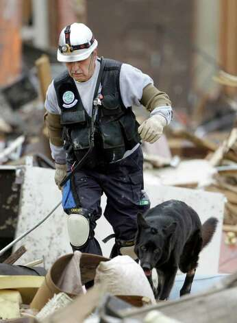 A search and rescue team member  looks for victims at a devastated apartment complex in Joplin, Mo.  Thursday, May 26, 2011. An EF-5 tornado tore through much of the city Sunday, damaging a hospital and hundreds of homes and businesses and killing at least 125 people. (AP Photo/Charlie Riedel) Photo: Charlie Riedel
