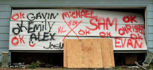 Names spray painted on a garage door indicate the status of residents of a home in a devastated Joplin, Mo. neighborhood Thursday, May 26, 2011. An EF-5 tornado tore through much of the city Sunday, damaging a hospital and hundreds of homes and businesses and killing at least 125 people. (AP Photo/Charlie Riedel) Photo: Charlie Riedel