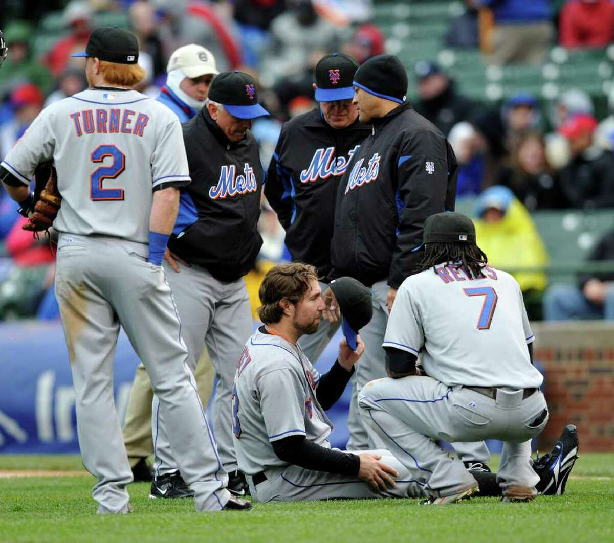 New York Mets starting pitcher R.A. Dickey, center, sits on the ground after getting injured against the Chicago Cubs during the third inning of a baseball game Thursday, May 26, 2011, in Chicago. (AP Photo/Jim Prisching)