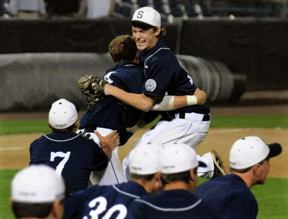 Staples celebrates its 7-6 win over St. Joseph, during FCIAC boys baseball semi-final action at the Ballpark at Harbor Yard in Bridgeport on Thursday May 26. 2011. In back is pitcher Jimmy Kopack embracing cather Mike McGowan. Photo: Christian Abraham / Connecticut Post