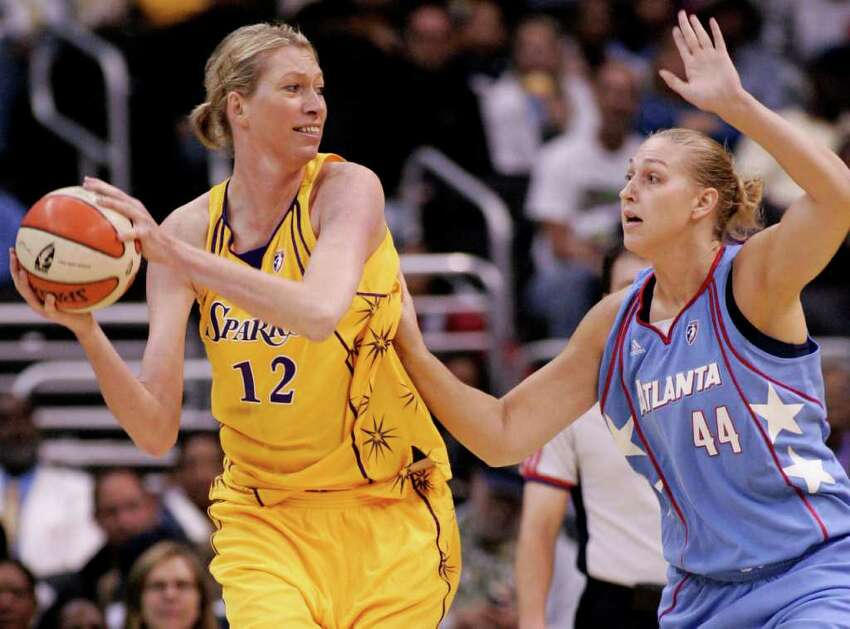 Los Angeles Sparks' Margo Dydek, left, protects the ball as Atlanta Dream's Katie Feenstra, right, defends during Dream's 83-72 victory in a WNBA basketball game on Sept. 11, 2008, in Los Angeles. Dydek has died after suffering a heart attack a week ago and being placed in a medically induced coma. Cathy Roberts, the operations manager for the Northside Wizards in the Queensland Basketball League, where Dydek was head coach, told The Associated Press that Dydek, 37, died early Friday May 27, 2011..