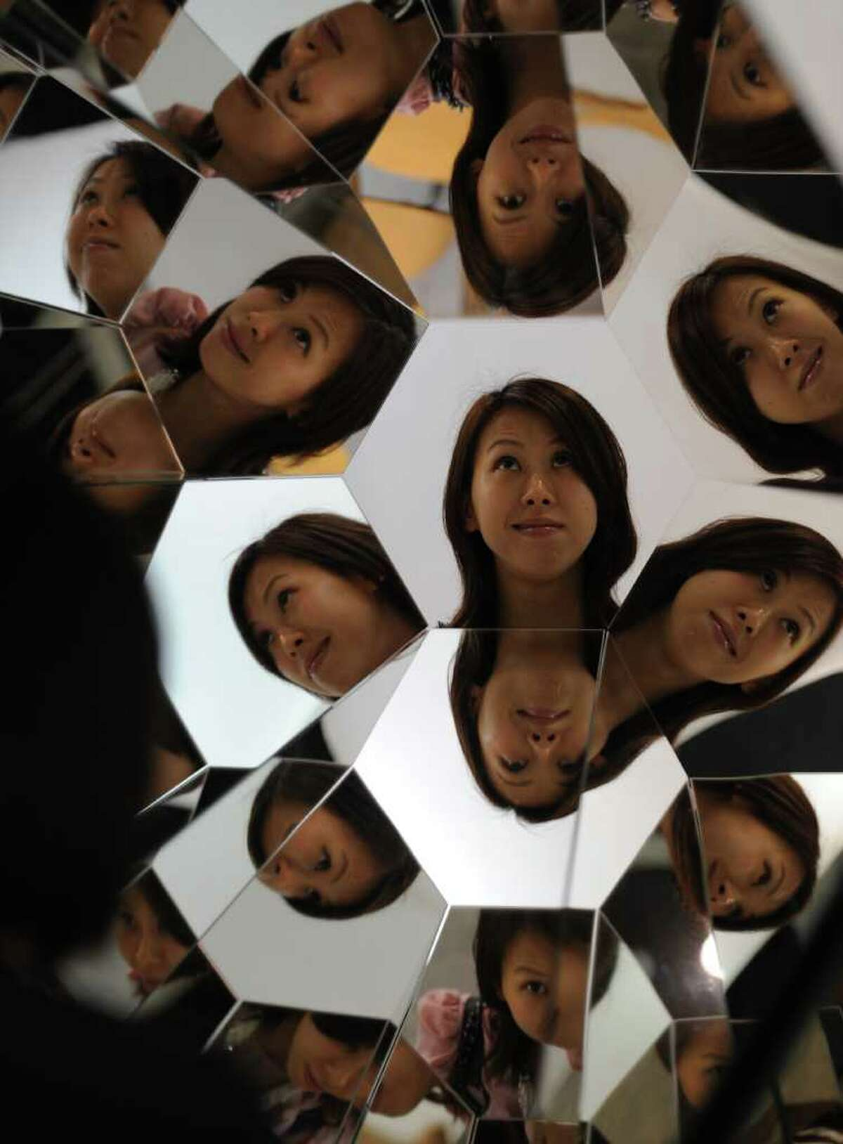 A woman looks at a work entitled 'Your Plural View' by Olafur Eliasson featuring a mirror using stainless steel and aluminum at the Hong Kong International Art Fair in Hong Kong on May 25, 2011.