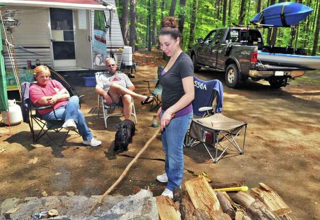 Nicole Davis, at right, stokes the campfire with Gail and Joe Gentile, all of Rotterdam, during their annual family Memorial Day camp out at Moreau Lake State Park Friday morning May 27, 2011.  (John Carl D'Annibale / Times Union) Photo: John Carl D'Annibale