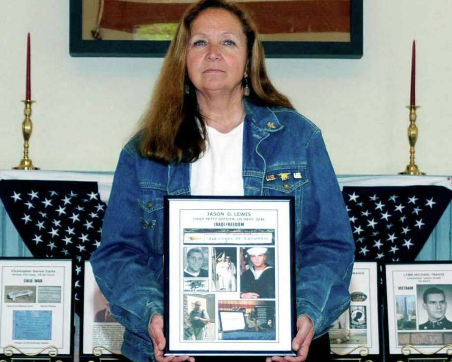 SPECTRUM/Jean Mariano of New Milford clutches a photo montage of her son, Jason Lewis, a Navy SEAL who was killed in combat during Operation Iraqi Freedom in 2007. May 14, 2011. Photo: Jay Weir / The News-Times Freelance
