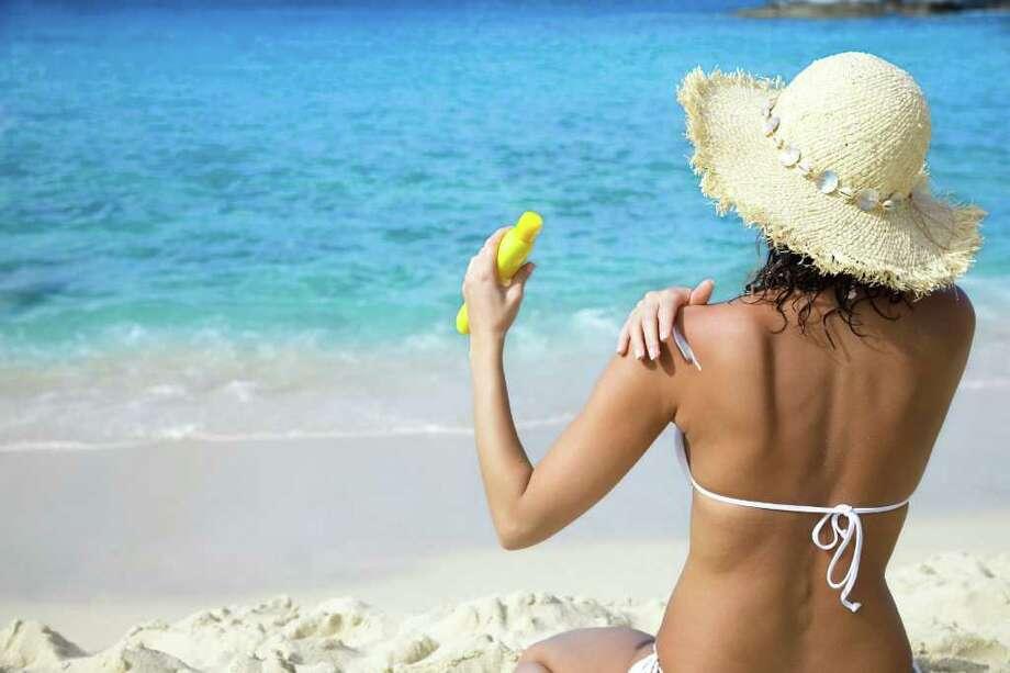 tan woman applying sunblock on a tropical beach; TANNING Photo: Christian Wheatley / handout / stock agency