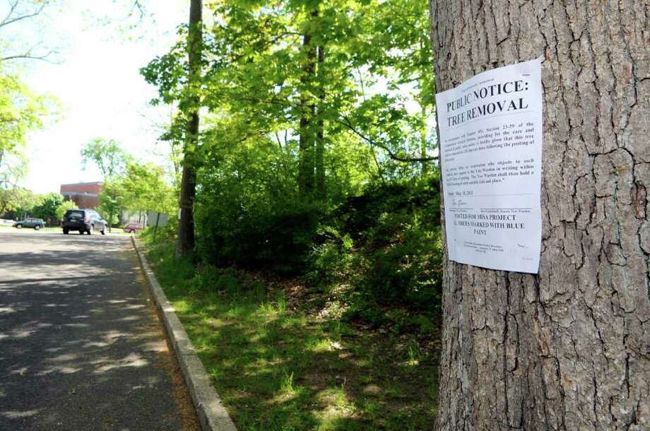 A public notice of tree removal posted on a tree at Greenwich High School on May 11, 2011. Greenwich Tree Warden Bruce Spaman ruled Friday, May 27, 2011, that 121 trees slated to be removed as part of the school's plan to upgrade its auditorium and music instruction space will only be removed if district officials agree to several conditions. Photo: File Photo / Greenwich Time File Photo