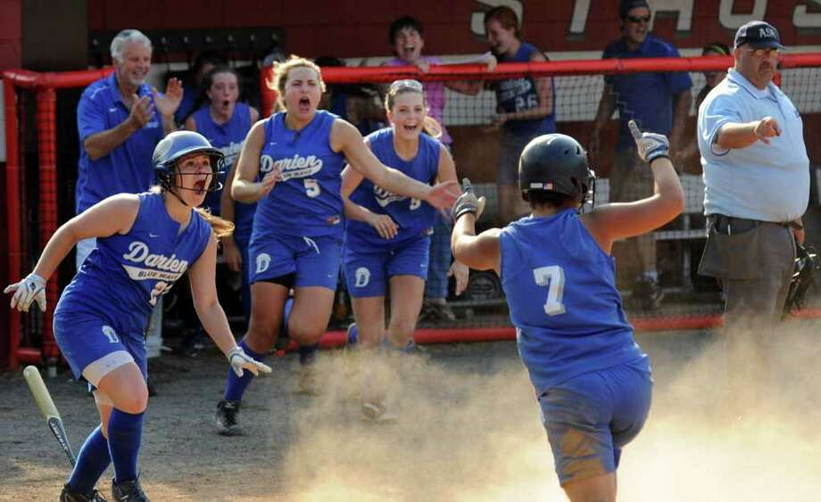 Darien celebrates its win over Fairfield Ludlowe, during the FCIAC girls softball final  at Fairfield University in Fairfield, Conn. on Friday May 27, 2011. Darien's #7 Nicole Buch slid into home plate to bring in the winning RBI to win the game 4-3. Photo: Christian Abraham / Connecticut Post