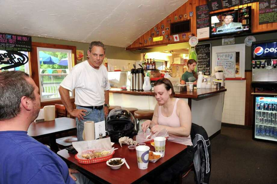 """Ron """"R.W."""" Wishna, of Ridgefield, center, owner of RW's BBQ in Brookfield, talks with dinner customers Anthony Mills, left, and Kate Johnston. Photo taken Friday, May 27, 2011. Photo: Carol Kaliff / The News-Times"""