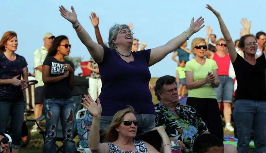 Francesca Watson (center) raises her arms in praise during a service held Sunday May 22, 2011 at the site of the former Verizon Wireless Amphitheater on Lookout Road. The River City Community Church will be moving from its location on Jones Maltsberger to the site of the former Verizon Wireless Amphitheater. JOHN DAVENPORT/jdavenport@express-news.net Photo: John Davenport/Express-News