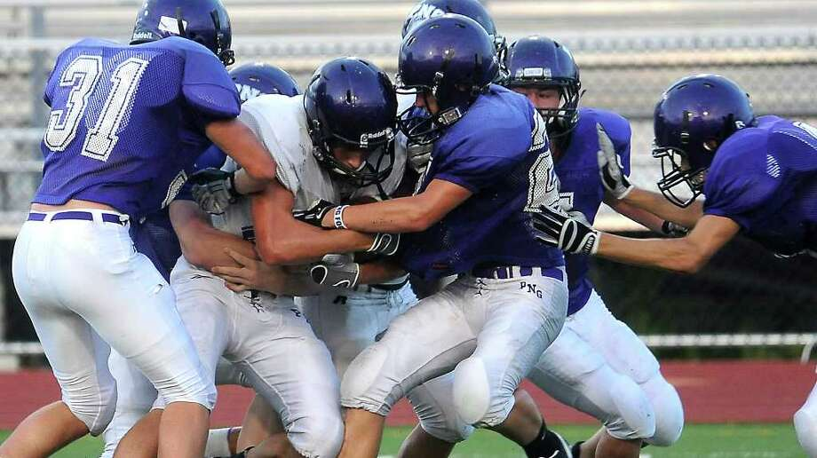 White's Logan Chipman tries to push through a host of Purple defenders during the Purple vs White spring game at PNG in Port Neches, Friday. Tammy McKinley/The Enterprise Photo: TAMMY MCKINLEY
