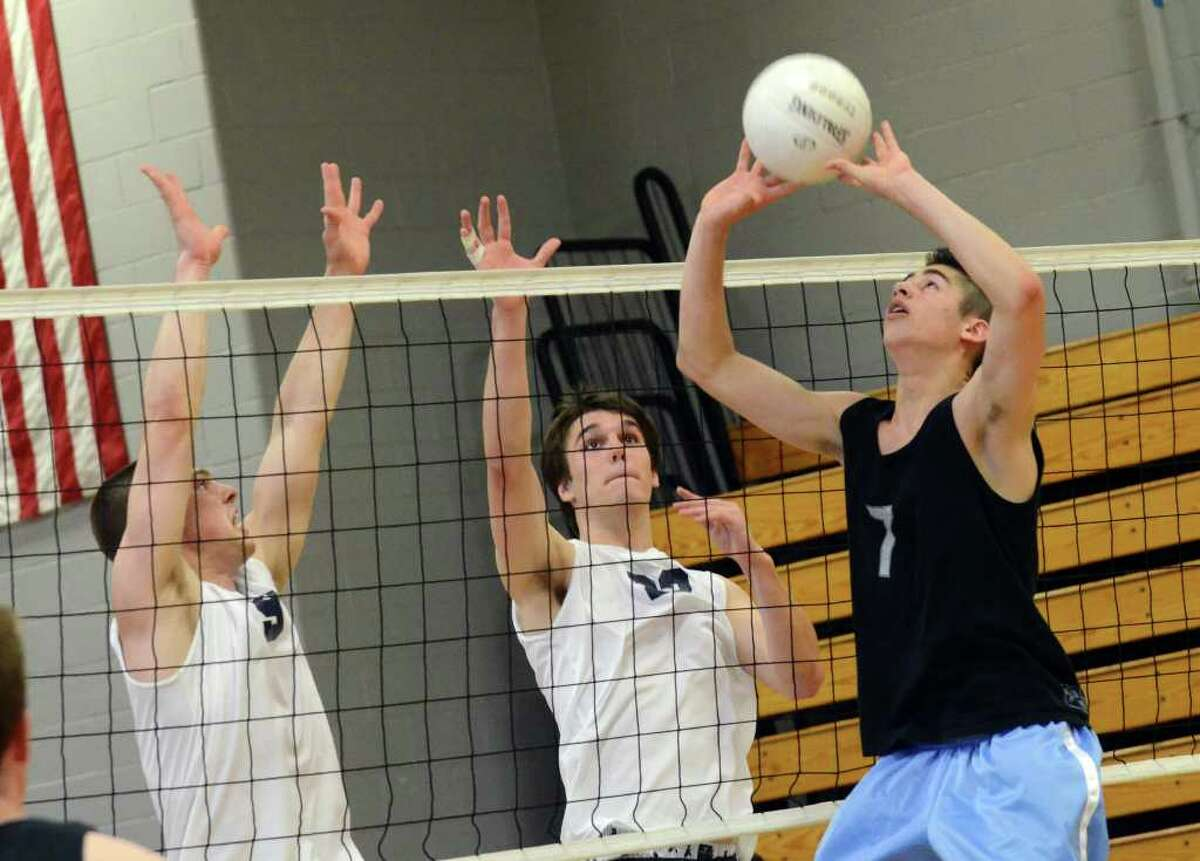 Darien's Matt Lee (7) sets the ball as Staples' Steven Denowitz and Andreas Bub (23) prepare to defend during the boys volleyball FCIAC championship match at Fairfield Ludlowe on Friday, May 27, 2011.