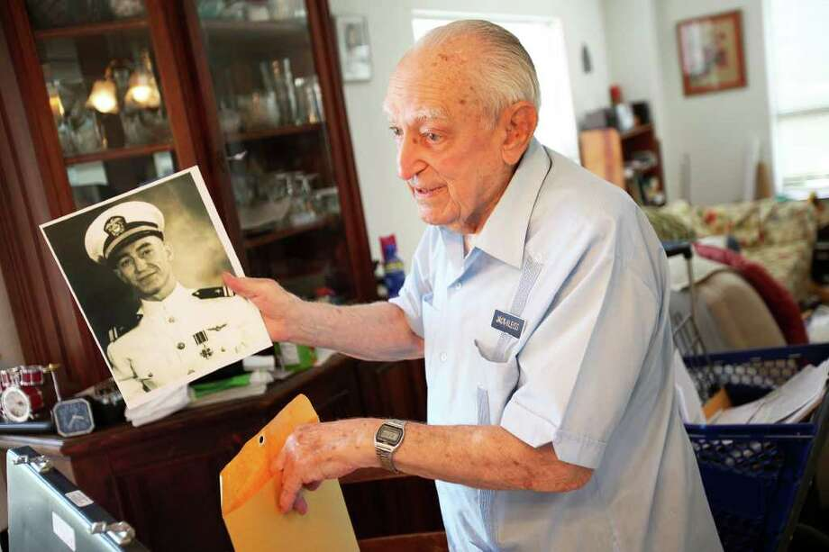 Capt. Norman J. Kleiss shows off a picture of himself taken after recieving the Distinguished Flying Cross at his apartment May 24, 2011. Kleiss recieved the medal from Fleet Admiral Chester Nimitz for bombing a cruiser in the Marshall Islands during World War II.  ANDREW BUCKLEY / abuckley@express-news.net Photo: ANDREW BUCKLEY, Andrew Buckley/Express-News / SAN ANTONIO EXPRESS-NEWS