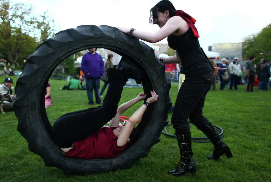 Nikki Hunter rolls friend Maggie in a tire during the 40th annual Northwest Folklife Festival. Photo: JOSHUA TRUJILLO / SEATTLEPI.COM