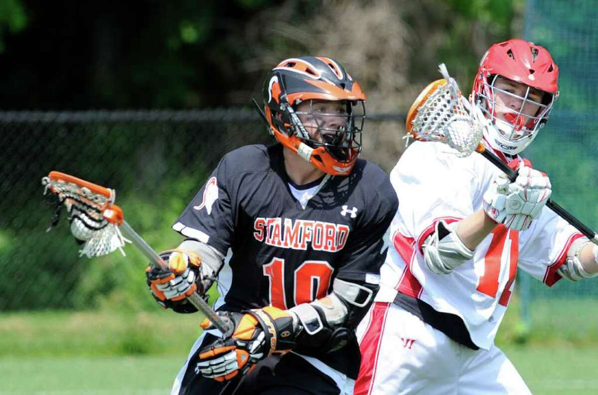 J.J. Bingham, # 10 of Stamford High School, left, mixes it up with Pete Cabrera , #11 of Greenwich High School, right, during Class L boys lacrosse playoff game between Greenwich High School and Stamford High School at Greenwich High School, Saturday morning, May 28, 2011.