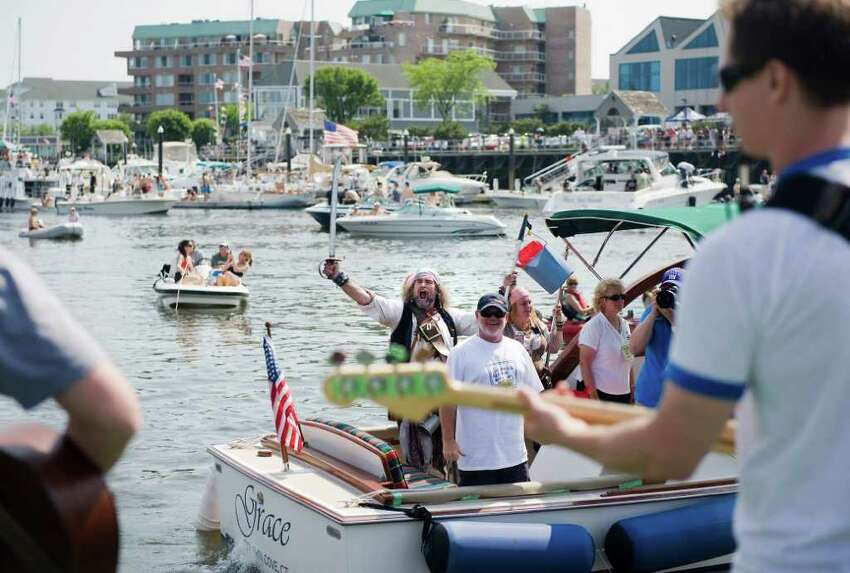 A boat full of 'pirates' goes by the stage as the Kovac Brothers band performs at the Stamford Harbor Live event in Stamford, Conn. on Saturday May 28, 2011. The event will benefit the Young Mariners Foundation.