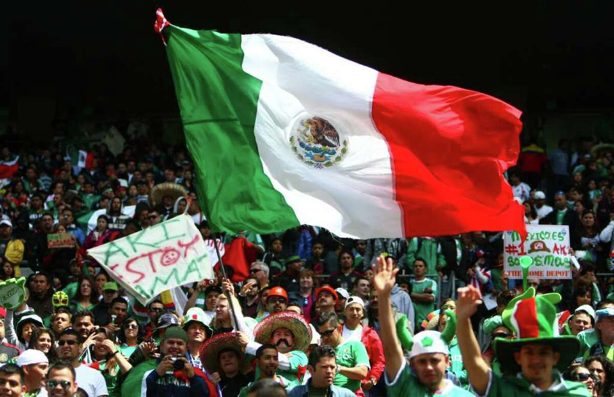A Mexico fan waves a large flag during the match against Ecuador.