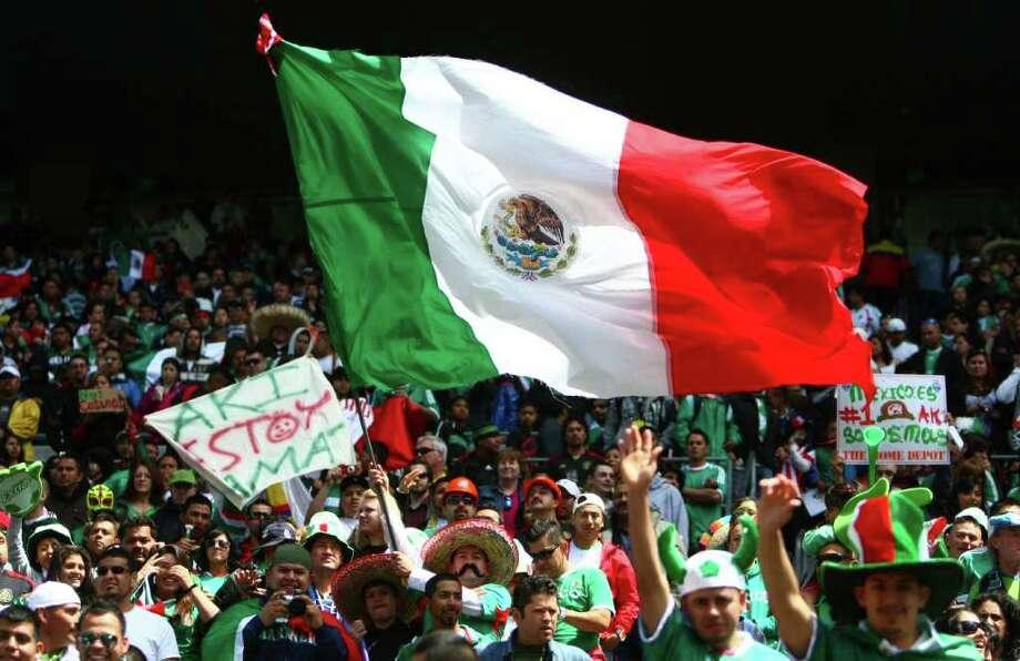 A Mexico fan waves a large flag  during the match against Ecuador. Photo: JOSHUA TRUJILLO / SEATTLEPI.COM