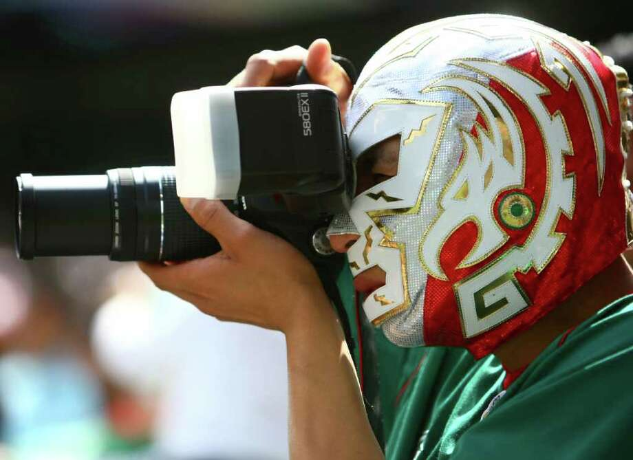 A fan, wearing a luchador mask, photographs the Mexican team. Photo: JOSHUA TRUJILLO / SEATTLEPI.COM