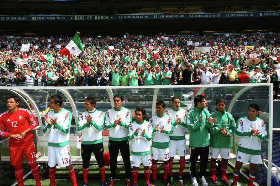 Mexico players applaud their national anthem before the match.
