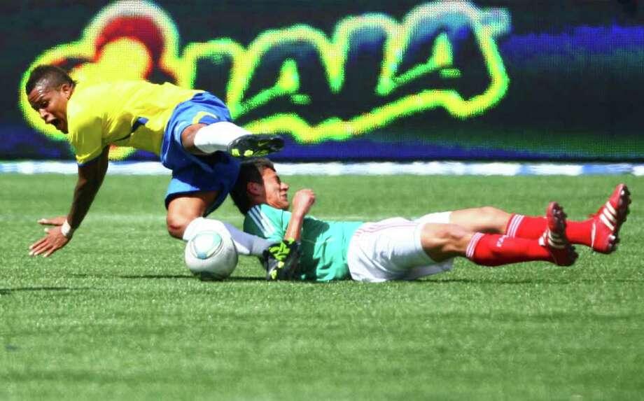 Ecuador player Michael Arroyo falls on top of Mexico player Hector Moreno during game action. Photo: JOSHUA TRUJILLO / SEATTLEPI.COM