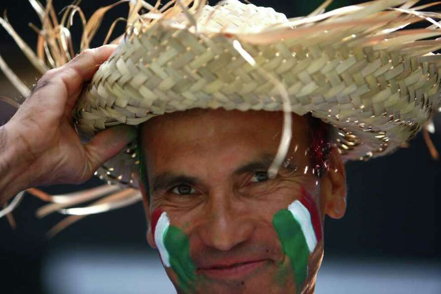 A fan sports the Mexican tri-color on his face during the friendly match against Ecuador.