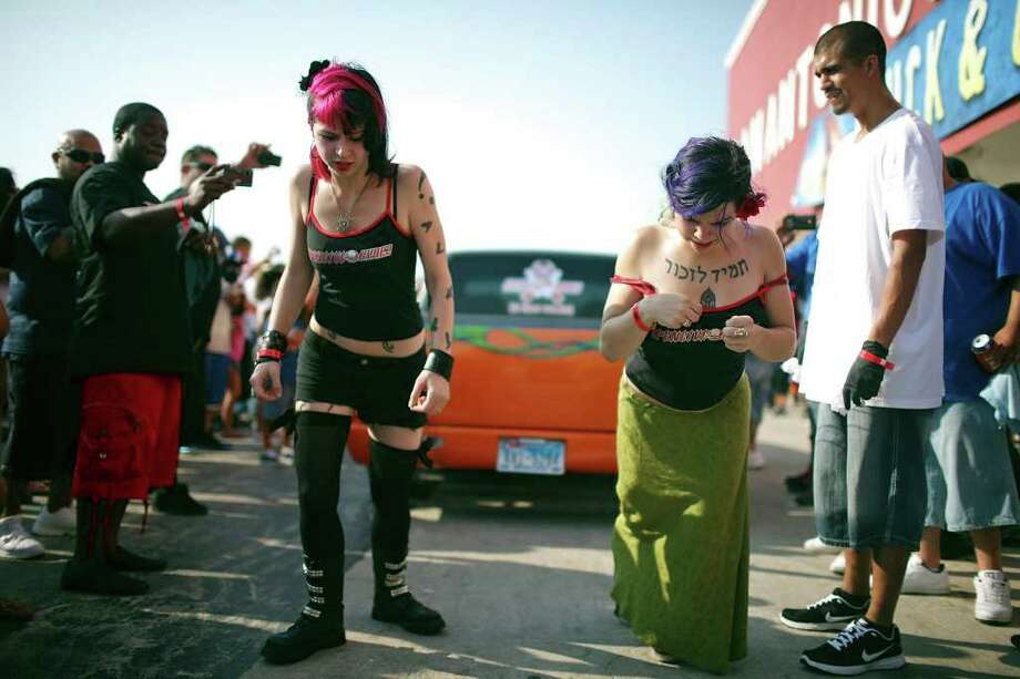 Haley Penalber, 21 (left), and Whitney Allen, 20, both from Austin, take part in a tug of war using suspension hooks in their backs during the 2011 Heat Wave Auto Fest held Saturday, May 28, 2011, at the San Antonio Event Center. The event, which runs through Sunday, May 29, 2011, included live entertainment, food and drinks and a tattoo expo. Photo: Edward A. Ornelas/Express-News