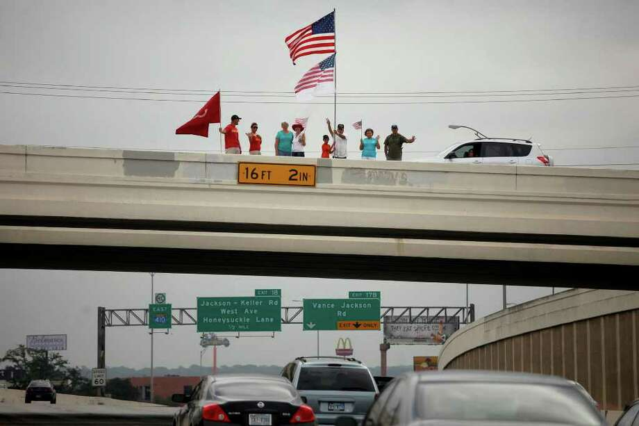 Robert Garcia (far right), a San Antonio firefighter and Iraq war veteran, is joined by family and friends to fly a flag over Loop 410 to honor fallen troops for Memorial Day. LISA KRANTZ/lkrantz@express-news.net Photo: LISA KRANTZ, Lisa Krantz/Express-News / SAN ANTONIO EXPRESS-NEWS