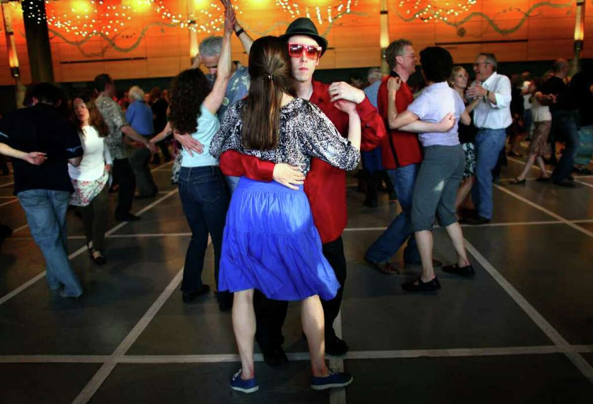 Kevin Buster dances with Michelle Mead in Fischer Pavilion during the Northwest Folklife Festival on Saturday, May 28, 2011 at the Seattle Center. The annual Memorial Day weekend festival is celebrating its 40th anniversary. It continues through Monday.