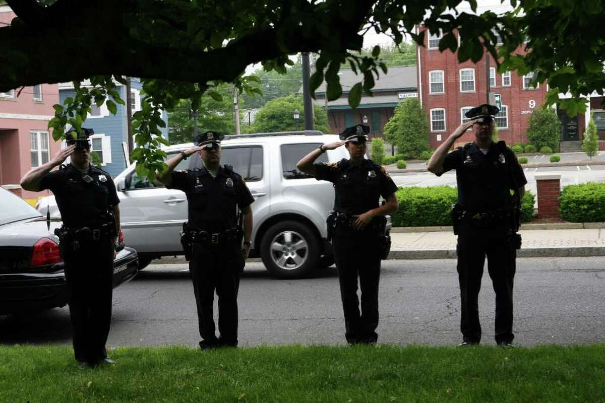 Milford police officers salute during the Milford wreath laying ceremony on Sunday, May 29, 2011.V
