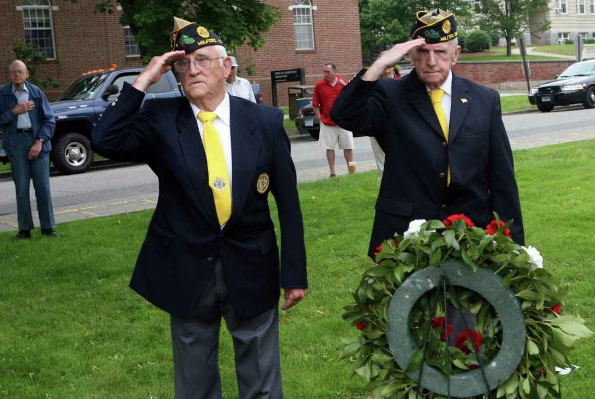 Veterans, Wayne Carson, left, and Bob Sherrick , salute during the Milford wreath laying ceremony on Sunday, May 29, 2011.